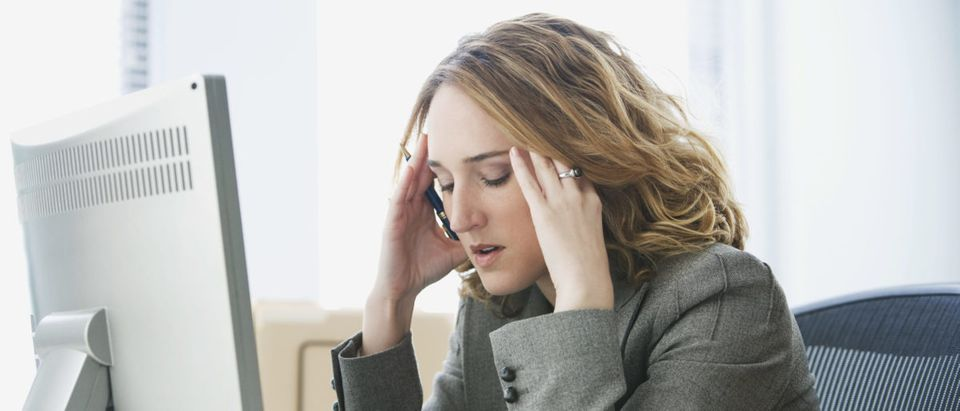 A woman is stressed in front of a computer. Shutterstock image via user micro10x
