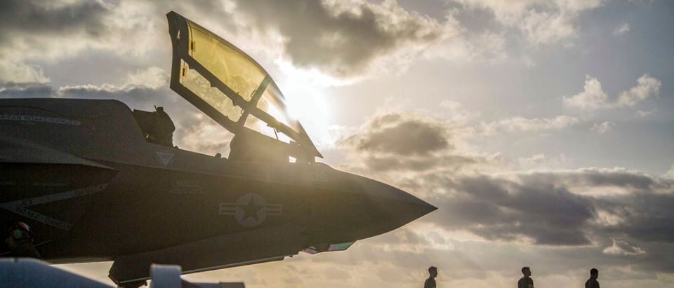 180922-M-PK127-1001 GULF OF ADEN (Sept. 22, 2018) A Marine Corps F-35B Lightning II sits on the flight deck of the Wasp-class amphibious assault ship USS Essex (LHD 2) while Marines with Marine Fighter Attack Squadron 211, 13th Marine Expeditionary Unit (MEU), prepare for flight operations. The Essex Amphibious Ready Group and 13th MEU are the first U.S. Navy/Marine Corps team to deploy to the U.S. 5th Fleet area of operations with the transformational warfighting capabilities of the F-35B Lightning II, making it a more lethal, flexible and persistent force, leading to a more stable region for our partner nations (U.S. Marine Corps photo by Cpl. Francisco J. Diaz Jr./Released)