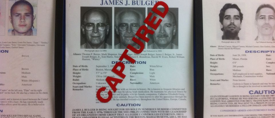 """A most wanted poster for FBI Most Wanted fugitive and accused Boston crime boss James """"Whitey"""" Bulger, is seen marked """"CAPTURED"""" on a wall with other fugitive wanted posters at FBI headquarters in Washington, June 23, 2011. On the run for 17 years, Bulger and his longtime girlfriend were finally caught in California by the Federal Bureau of Investigation on Wednesday. REUTERS/FBI/Handout"""