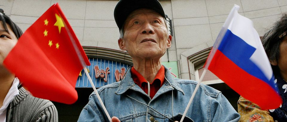 An elderly man holds Chinese and Russian