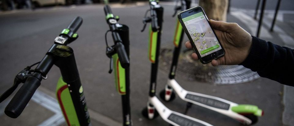 A man shows the mobile application allowing to check the availability of electric scooters of the US company Lime on the day of their launch in Paris on June 22, 2018. CHRISTOPHE ARCHAMBAULT/AFP/Getty Images