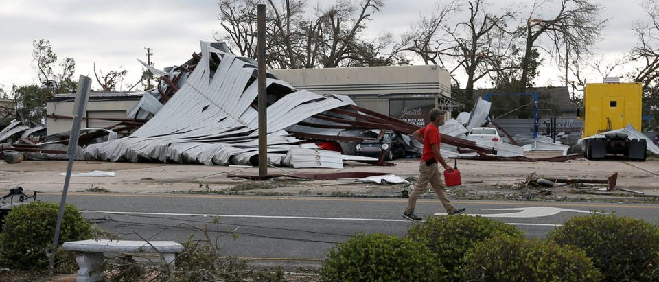 A man walk past buildings damaged by Hurricane Michael in Panama City, Florida, U.S. October 11, 2018. REUTERS/Jonathan Bachman