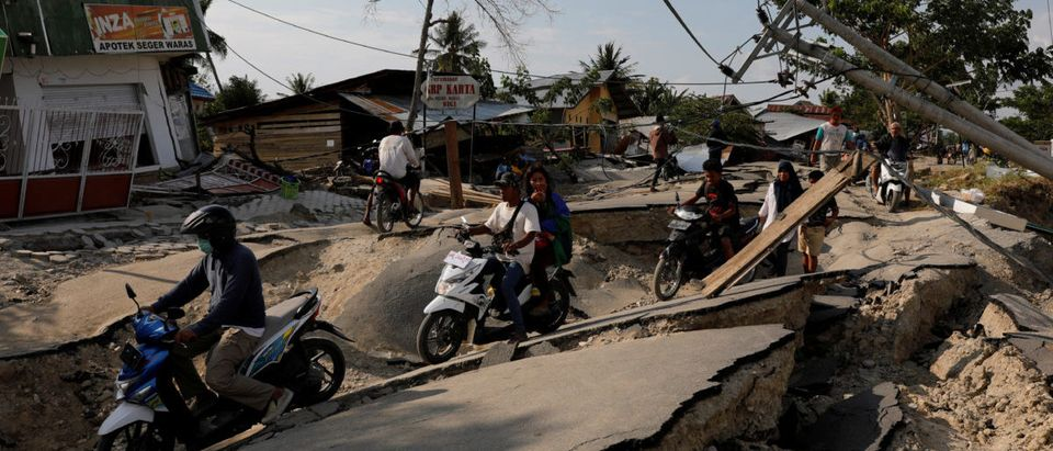 People drive motorcycles through a damaged road after an earthquake hit Biromaru village in Sigi