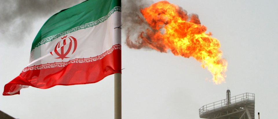 FILE PHOTO: A gas flare on an oil production platform in the Soroush oil fields is seen alongside an Iranian flag in the Gulf