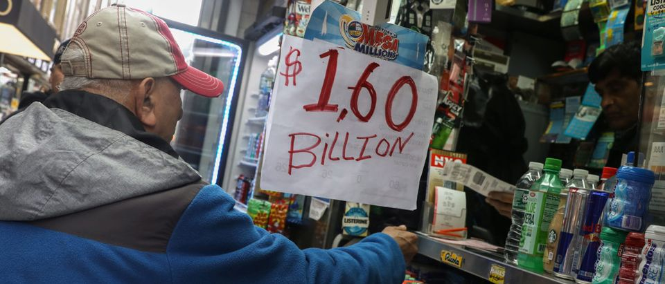 A man buys tickets for Tuesday's Mega Millions lottery drawing after the jackpot exceeded $1.6 billion in New York City