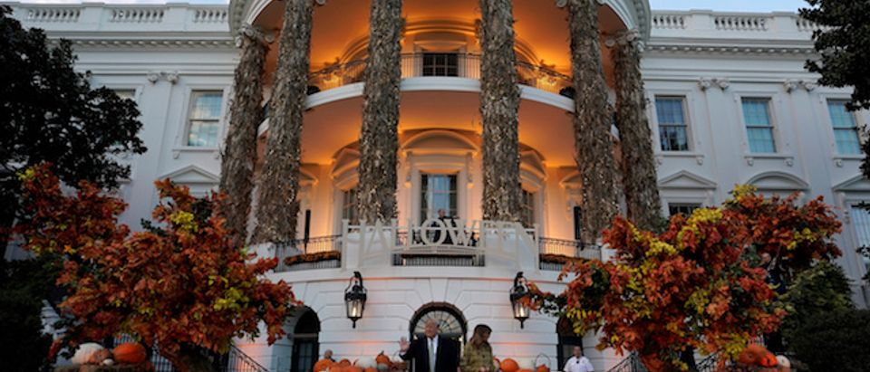 U.S. President Donald Trump and U.S. first lady Melania Trump hand out Halloween candy to trick or-treaters at the White House in Washington, U.S., October 28, 2018. REUTERS/Joshua Roberts