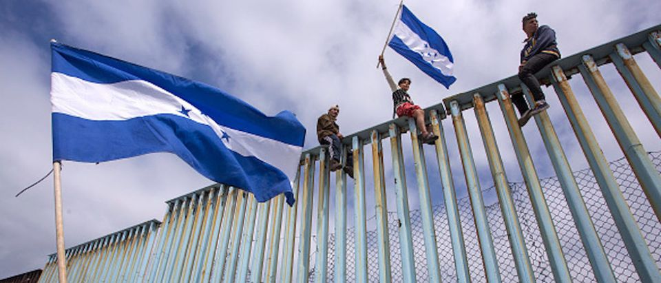 People hold Honduran flags at the border fence during a rally with members of a caravan of Central American asylum seekers and supporters on April 29, 2018 in Tijuana, Baja California Norte, Mexico