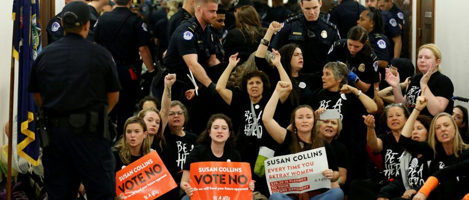 Demonstrators chant before being arrested as they protest against U.S. Supreme Court nominee Brett Kavanaugh in front of the office of Senator Susan Collins (R-ME) on Capitol Hill in Washington