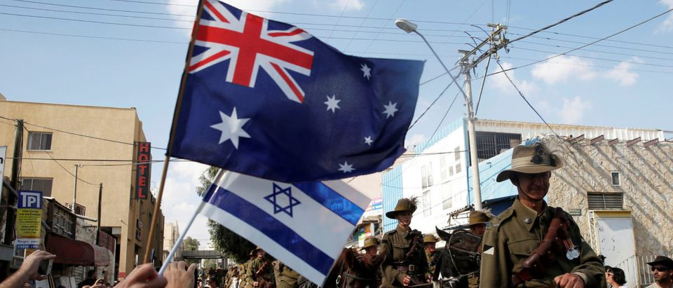 """FILE PHOTO: People wave Australian and Israelis flags as members of the Australian Light Horse Association ride pass them during a cavalry parade as part of events marking the centenary of the """"Battle of Beersheba"""", in Beersheba's Old City,"""