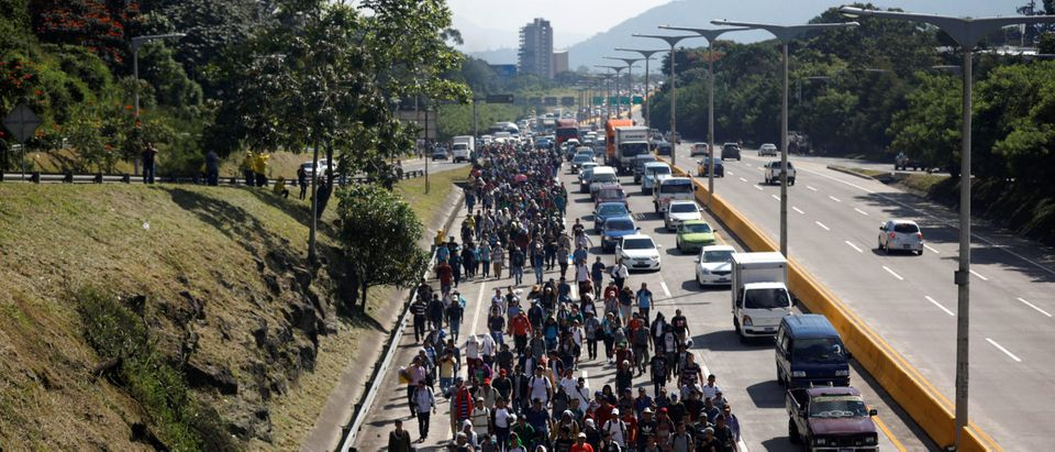 People walk in a caravan of migrants departing from El Salvador en route to the United States, in San Salvador