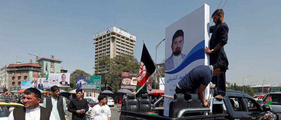 People hold a poster of a parliamentary candidate on the back of a truck during the first day of election campaign in Kabul, Afghanistan September 28, 2018. Picture taken September 28, 2018. REUTERS/Omar Sobhani - RC1D6E51C760