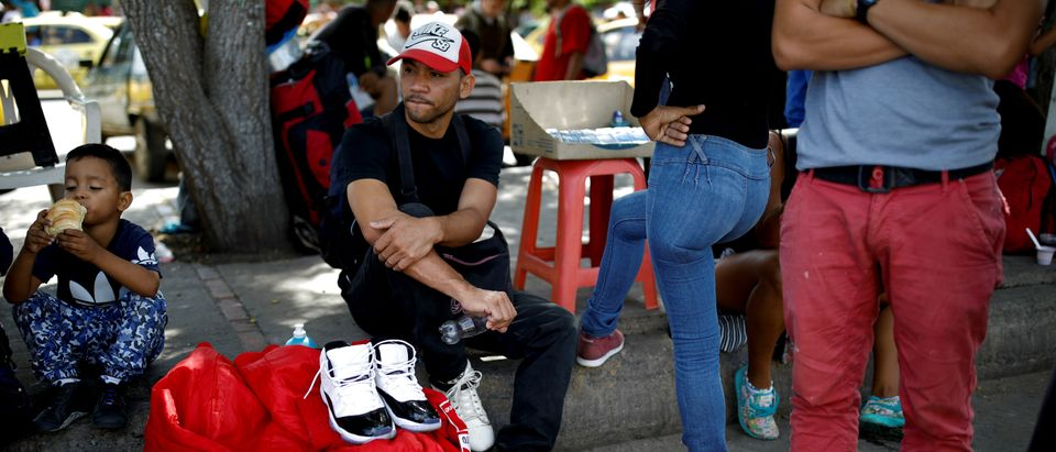 Dario Leal, 30, (C), a Venezuelan baker who entered Colombia by crossing the Tachira river, sits on the sidewalk next to a pair of shoes being sold by a friend, on his second day in Villa del Rosario, Colombia August 25, 2018. Leal spent two days hoping that relatives in Bogota would help by wiring him money, but eventually decided he had no option but to walk to the Colombian capital. Leal could not bring himself to tell his nine-year old son Diogel that he was emigrating. REUTERS/Carlos Garcia Rawlins