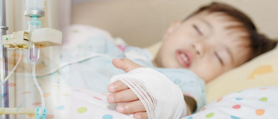 Sick kid with IV (Shutterstock/Jesada)