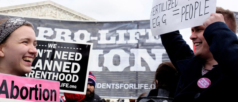 A pro-life demonstrator (L) and a pro-choice counter-protester (R) laugh together as the annual March for Life concludes at the U.S. Supreme Court in Washington, DC, U.S. Jan. 27, 2017. REUTERS/James Lawler Duggan