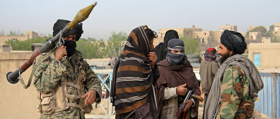 Members of the Taliban gather at the site of the execution of three men accused of murdering a couple during a robbery in Ghazni Province