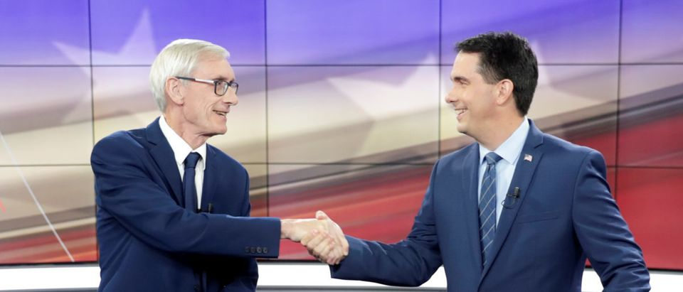 Democratic challenger Tony Evers and Wisconsin Gov. Scott Walker shake hands during a media availability before the start of the gubernatorial debate in Madison Wisconsin