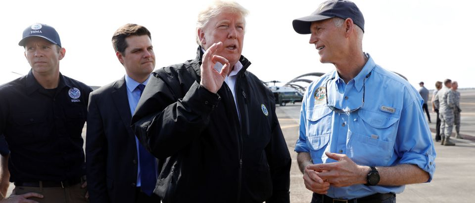 U.S. President Donald Trump stands with FEMA Administrator Brock Long (L) and U.S. Rep Ron DeSantis (R-FL) as he talks to Florida Governor Rick Scott (R) after the president arrived to tour storm damage from Hurricane Michael at Eglin Air Force Base, Florida, U.S., October 15, 2018. REUTERS/Kevin Lamarque