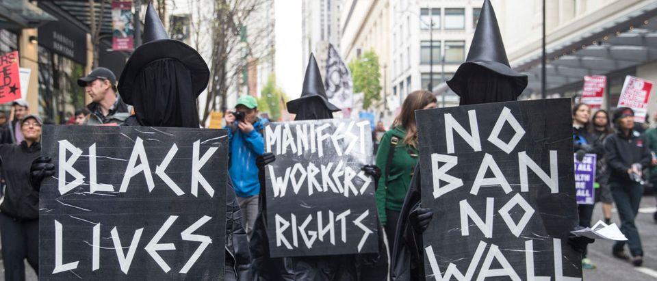 Marchers wearing witches hats and carrying signs make their way through downtown during the Workers and Immigrant Rights March on May 1, 2017 in Seattle, Washington. Hundreds took part in the annual May Day event. (Photo by Stephen Brashear/Getty Images)