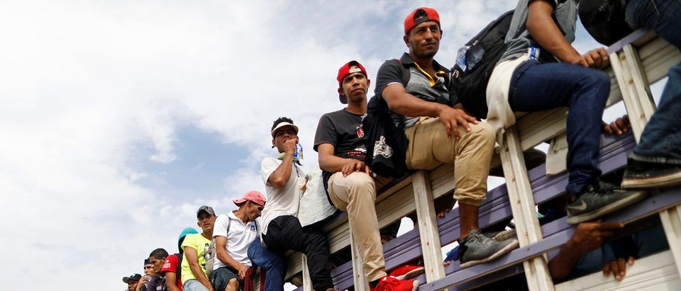 Honduran migrants, part of a caravan trying to reach the U.S., are pictured on a truck during a new leg of their travel in Chiquimula