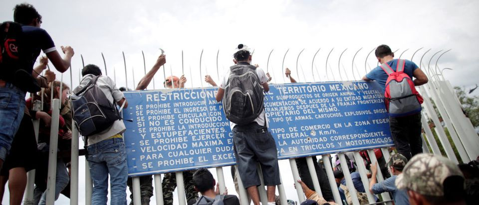 Honduran migrants, part of a caravan trying to reach the U.S., climb a fence in an effort to enter Mexico after storming a border checkpoint in Guatemala, in Ciudad Hidalgo