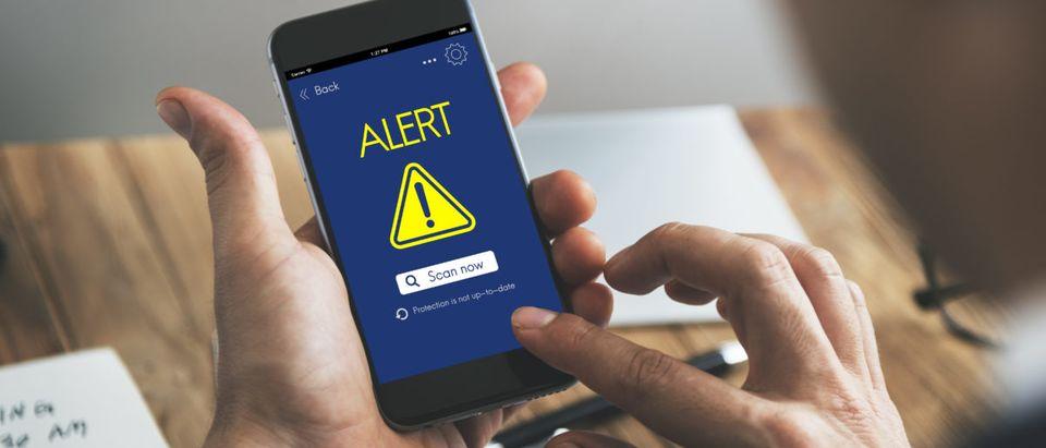A man receives a message alert. Shutterstock image via user Rawpixel.com