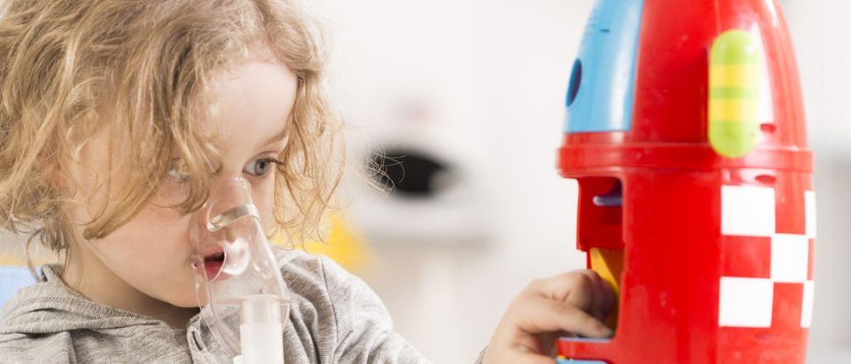 A child with cystic fibrosis plays with a toy rocket. Shutterstock image via user Photographee.eu