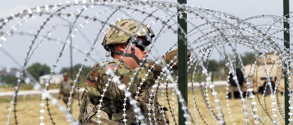 A U.S. Army soldier installs barbed wire fence for an encampment to be used by the military near the U.S. Mexico border in DonnaTexas