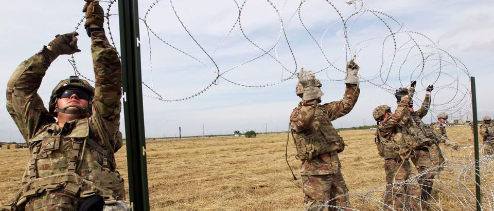 U.S. Army soldiers deploying barbed wire.