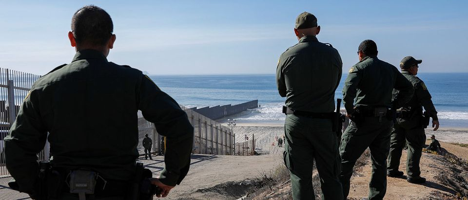 U.S. border patrol agents gather to look over the border fence between Mexico and the United States, where they expect a large group of caravan migrants to gather on Sunday, at Border State Park in San Diego