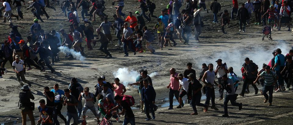 Migrants, part of a caravan of thousands from Central America trying to reach the United States, run from tear gas released by U.S border patrol, near the border fence between Mexico and the United States in Tijuana