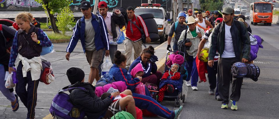 Migrants, part of a caravan of thousands traveling from Central America en route to the United States, hitchhike as they make their way to Queretaro from Mexico City