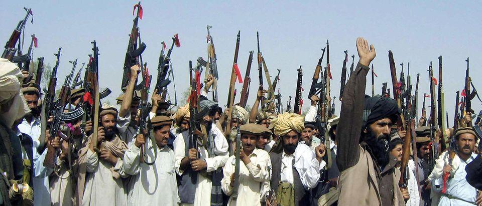 Pakistani tribesmen raise their red-ribb
