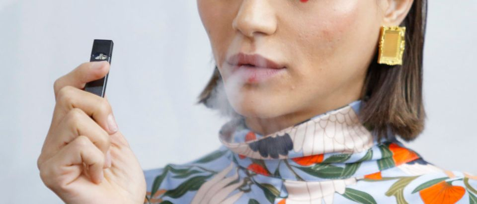 A model smokes a vape before the Snow Xue Gao Spring Summer 2018 show during New York Fashion Week on September 8, 2017 in New York. EDUARDO MUNOZ ALVAREZ/AFP/Getty Images