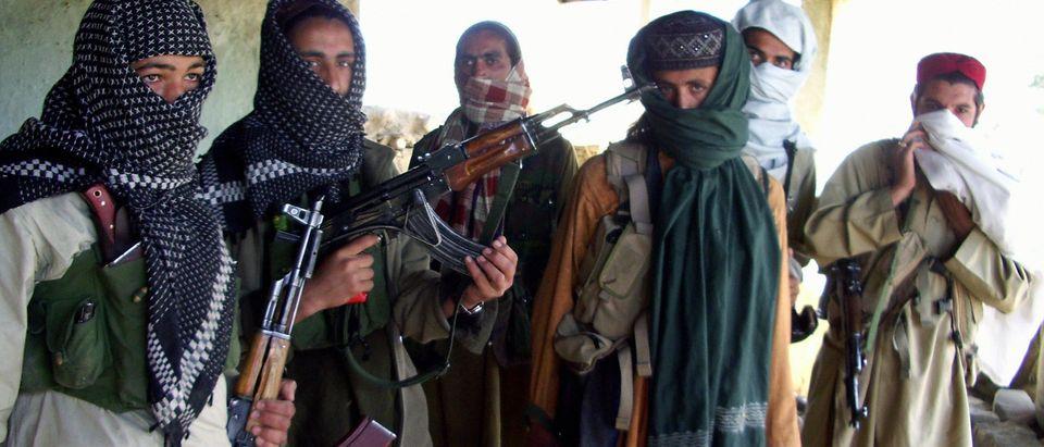 Armed Pakistani Taliban gather at a hide
