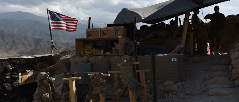 "In this photo taken on July 7, 2018, US Army soldiers from NATO looks on as U.S. flag flies in a checkpoint during a patrol against Islamic State militants at the Deh Bala district in the eastern province of Nangarhar Province. - A US soldier was killed and two others wounded in an ""apparent insider attack"" in southern Afghanistan on July 8, NATO said, the first such killing in nearly a year. (Photo by WAKIL KOHSAR / AFP)"