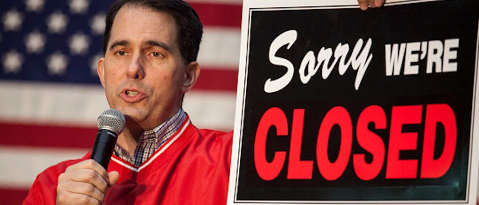 Governor Scott Walker (WI-R) holds a sign that reads 'sorry we're closed' as he speaks to supporters at a last minute get out the vote rally the night before the midterm elections