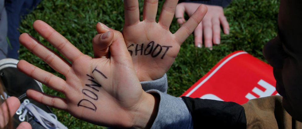 "A student intertwines her hands to read ""Don't Shoot"" during a rally at the U.S. Capitol in Washington"
