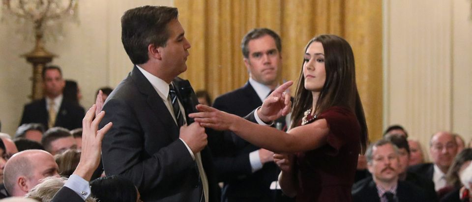 White House intern reaches for microphone held by CNN's Acosta as he questions U.S. President Trump during news conference in Washington