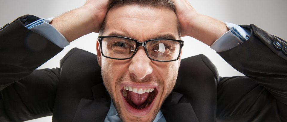 Closeup portrait of angry, frustrated man, pulling his hair out. (BlueSkyImage/Shutterstock)