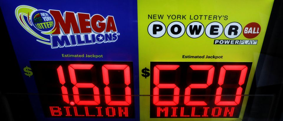 Signs display the jackpots for Friday's Mega Millions and Wednesday's Powerball lottery drawings in New York