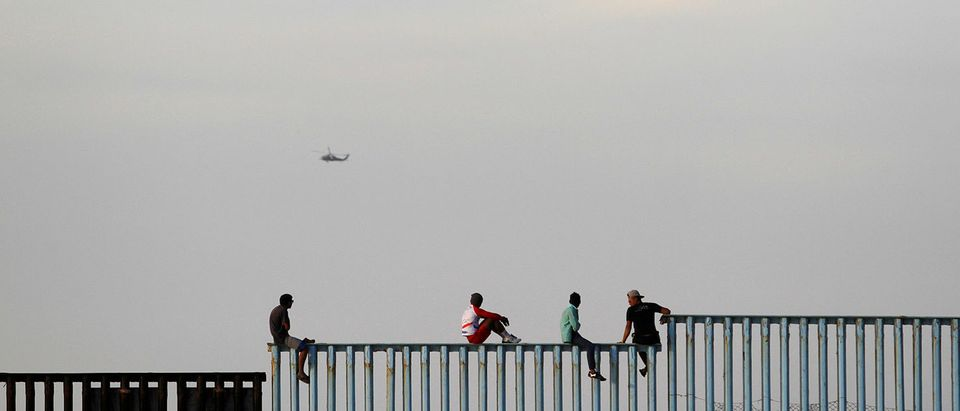 Migrants sit on top of the border fence between Mexico and the United States after arriving in Tijuana