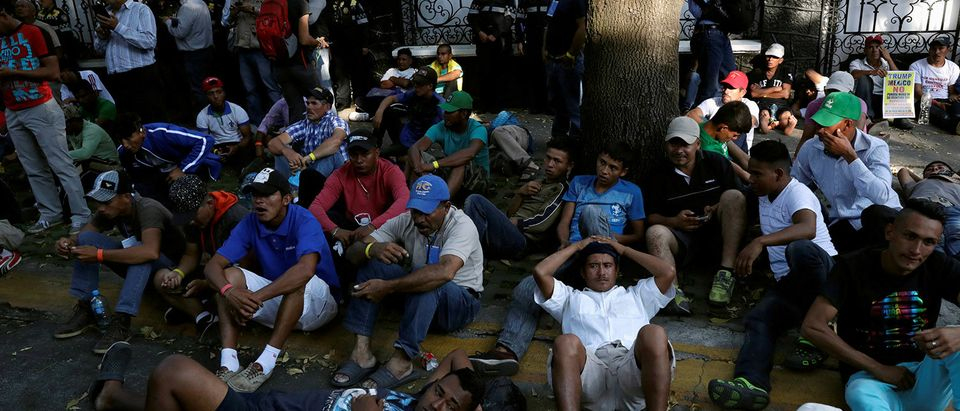 FILE PHOTO: Migrants, part of a caravan traveling from Central America en route to the United States, wait outside a UN Refugee Agency (UNHCR) office during a march demanding buses to take them to the U.S. border, in Mexico City
