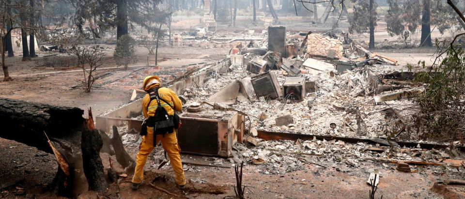 A firefighter extinguishes a hot spot in a neighbourhood destroyed by the Camp Fire in Paradise, California, U.S., Nov. 13, 2018. REUTERS/Terray Sylvester