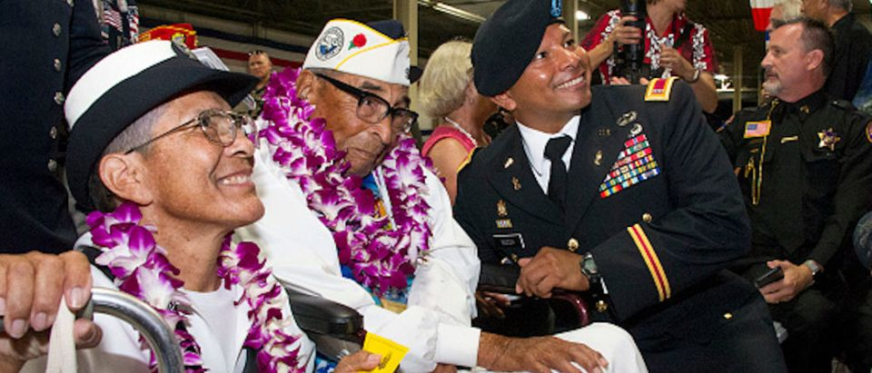Pearl Harbor survivor Ray Chavez (C) sits with his daughter Kathleen Chavez (L) and Chief Warrant Officer 4 Dorian Bozza (R) during a ceremony commemorating the 75th anniversary of the attack on Pearl Harbor