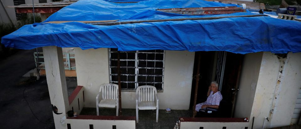 Lucila Cabrera, 86, sits at the porch of her house covered by plastic tarps over a damaged roof by Hurricane Maria, a year after the storm devastated Puerto Rico, near Barceloneta, Puerto Rico, September 18, 2018. Picture taken Sept. 18, 2018. REUTERS/Carlos Barria
