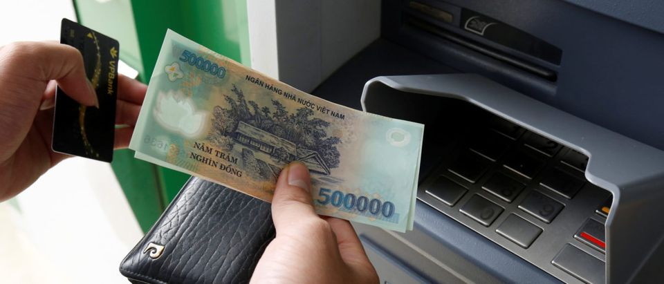 A man withdraws money from an ATM at a branch of VPBank in Hanoi, Vietnam