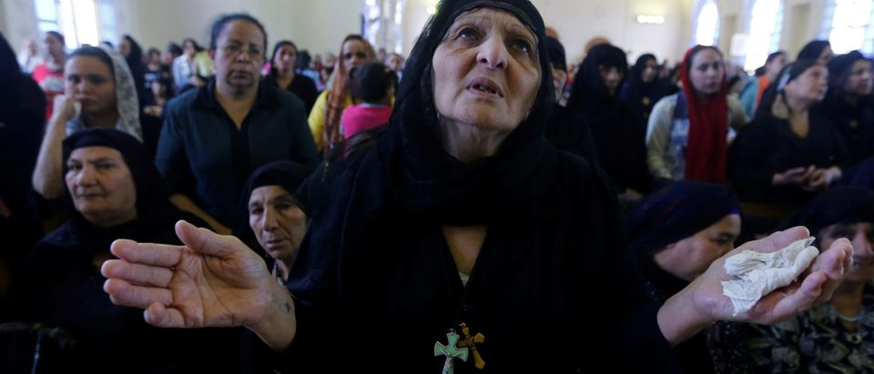 Coptic Egyptians pray during a funeral ceremony for the remains of the bodies of 20 Egyptian Christians beheaded in Libya by Islamic State in 2015, at a church in al-Our village south of Cairo