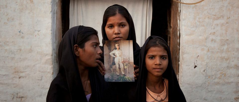 The daughters of Pakistani Christian woman Asia Bibi pose with an image of their mother while standing outside their residence in Sheikhupura Pakistan