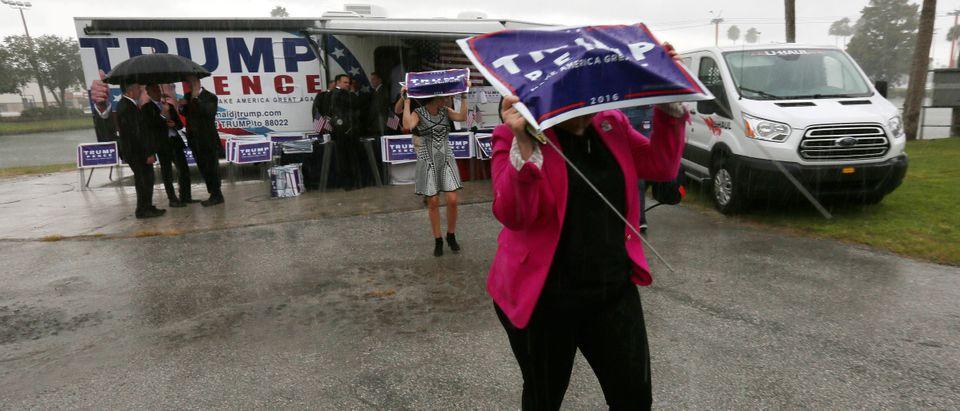 Campaign staff for Republican presidential nominee Donald Trump run into the venue in the rain under signs for a campaign rally in Tampa