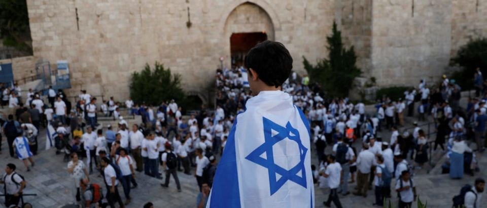 A boy wrapped with Israel's national flag is seen during a parade marking Jerusalem Day